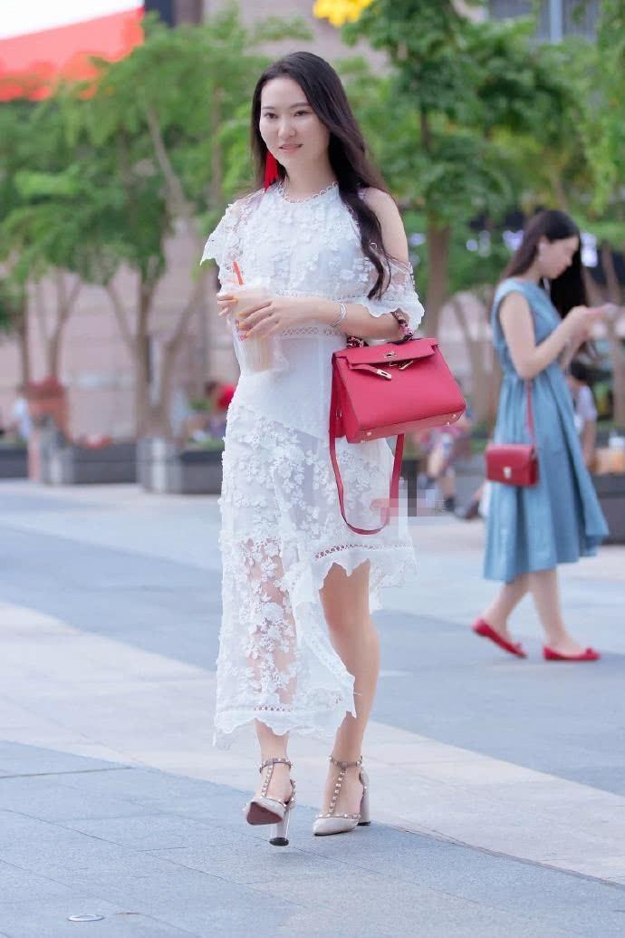 路人街拍:小姐姐穿着一件不规则长裙,脸上的微笑养眼又甜美!