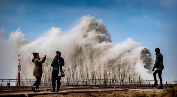 荷兰海岸遇风暴掀起巨浪 民众淡定拍照