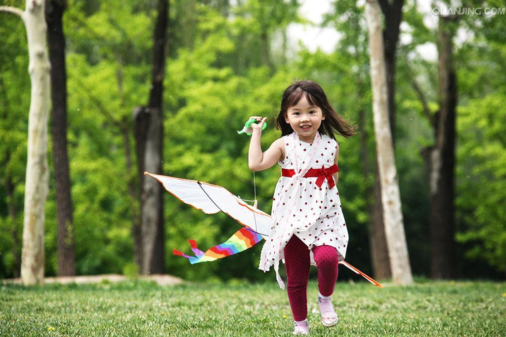 一个小女孩在户外放风筝_全景图片图片